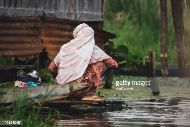 view of woman wash a dish at traditional floating market at dal lake of kashmir, india - shaifulzamri stock pictures, royalty-free photos & images