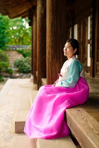 View of woman wearing Korean traditional clothes and sitting on a wooden porch - gettyimageskorea