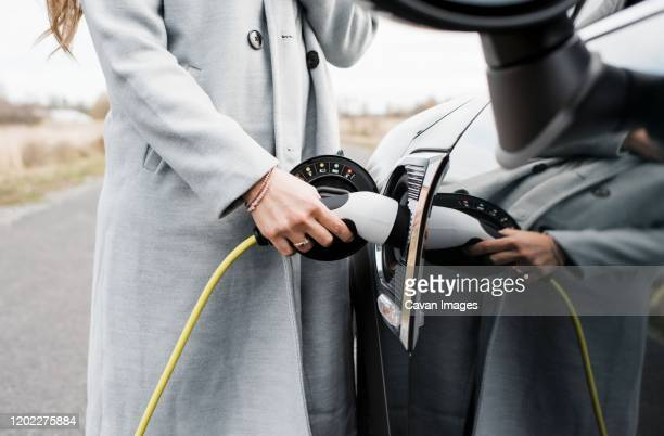 view of woman's hand plugging in charging lead to her electric car - electric car stock pictures, royalty-free photos & images
