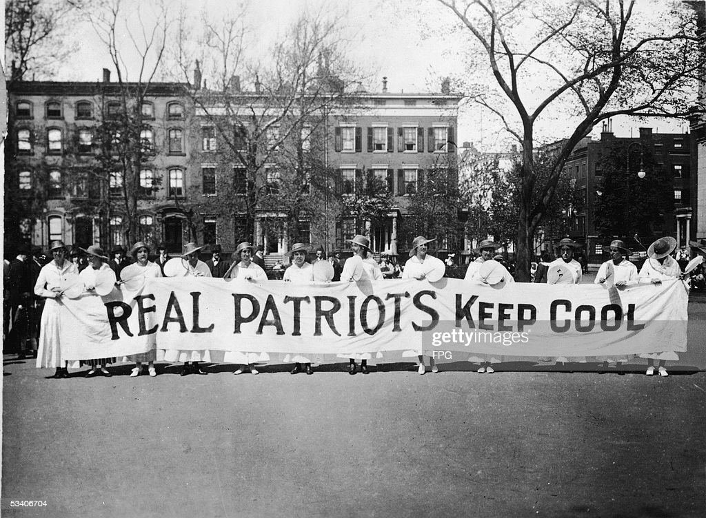 View of women from the Woman's Peace Party (later renamed the Women's International League for Peace and Freedom) as they stand and hold a banner which reads 'Real Patriots Keep Cool' to demonstate against US involvment in World War I, probably Washington DC, late 1910s.