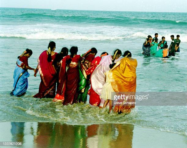 View of women in colorful saris as they stand at the waters at a beach, Chennai, India, 2004.
