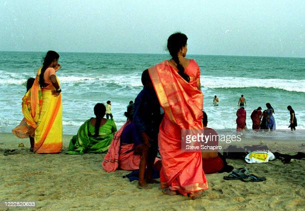 View of women in colorful saris on the sand at a beach, Mamallapuram, India, 2004.