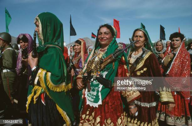 View of women in traditional Afghani clothing and carrying assault rifles as they march during the 10th anniversary celebration of the Saur...