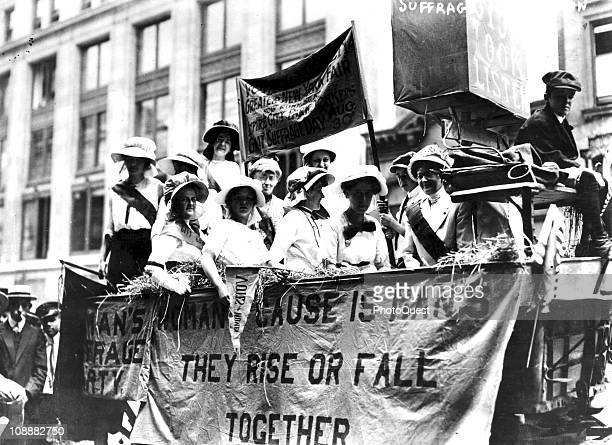View of women riding in a Hay Wagon float in a suffrage parade to New York's City Hall 1913 A banner hanging upon the float quotes Tennyson's phrase...