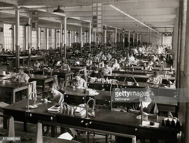 View of woment working in a garment factory, slip stitching the center seam of silk ties. Undated photograph.