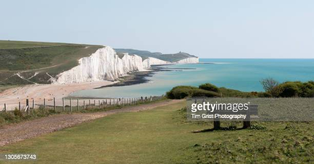 view of wooden bench seats overlooking the seven sisters cliffs and sea, east sussex, uk - hill stock pictures, royalty-free photos & images