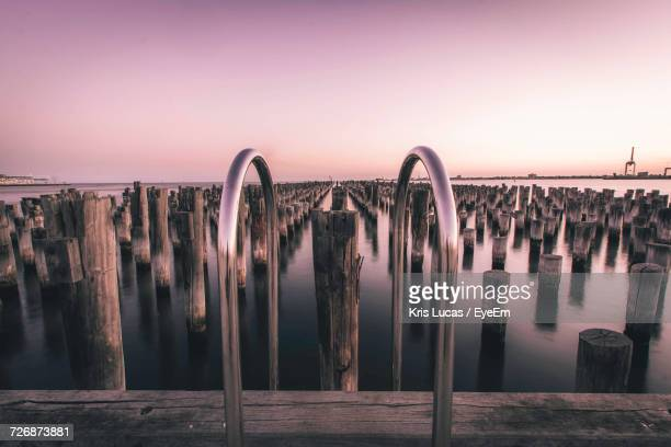 View Of Wooden Posts In Sea During Sunset