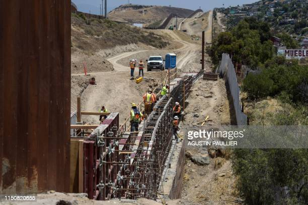 View of workers setting up the second wall in the MexicoUS border on June 18 in Tijuana Baja California Mexico