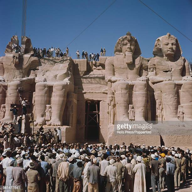 View of workers standing in front of the four statues of Pharoah Ramesses II at the Great Temple of Abu Simbel during final reassembly work after...