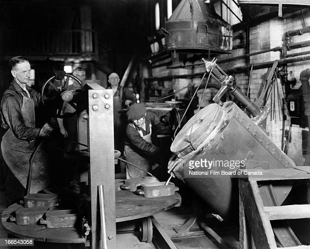 View of workers tilting furnaces and pouring molten gold into lingot moulds inside the Royal Canadian Mint Ottawa Ontario Canada 1938 Photo taken...