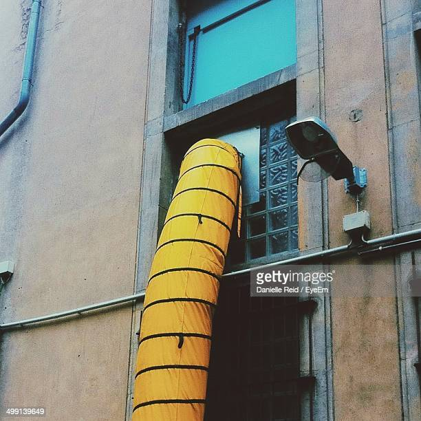 view of yellow pipe through building window - danielle reid stock pictures, royalty-free photos & images