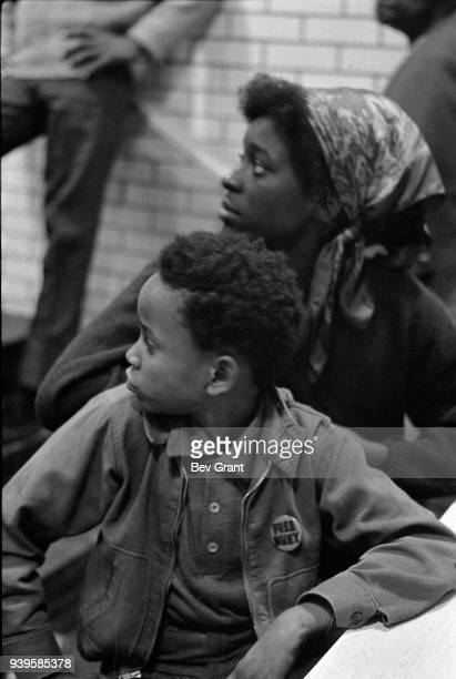 View of young boy with a 'Free Huey' button on his jacket and a woman as they attend a clothing drive sponsored by the Black Panther Party New York...