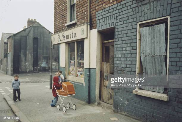 View of young children playing outside a corner shop selling sweets and confectionery in the predominantly republican Falls Road area of west Belfast...