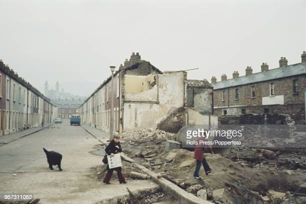 View of young children walking over wasteland at the end of a terraced street in the predominantly republican Falls Road area of west Belfast,...