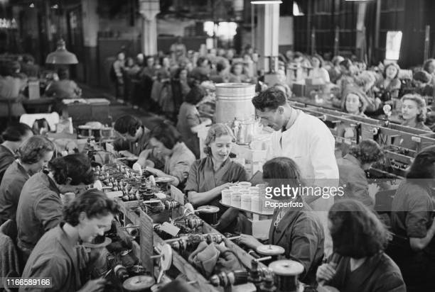 View of young female machine shop workers being offered a cup of tea at their benches in the machine shop as they manufacture parts for Supermarine...