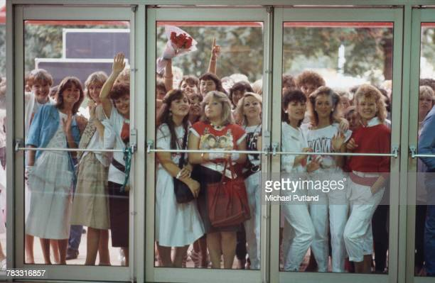 View of young female teenage pop fans standing outside the entrance doors of a venue as the wait to see a performance by the English pop duo George...