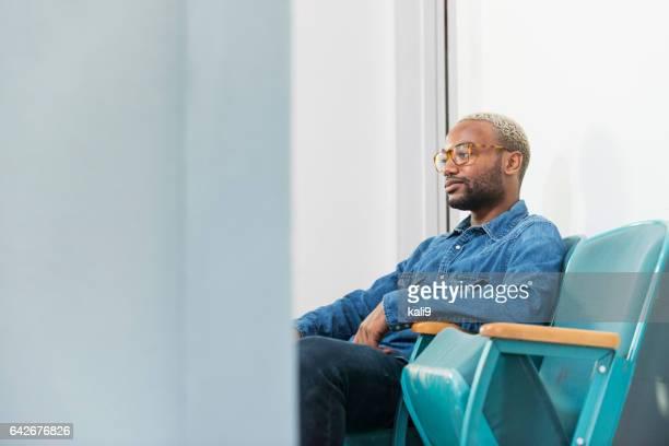 講堂で座っている戸口を若い男のビュー