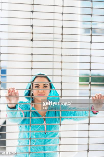 View of young woman in sports clothing, thru metal grate