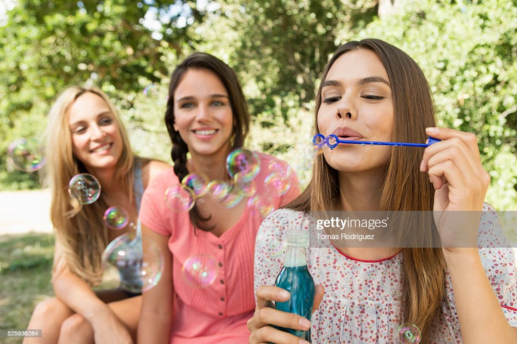 View of young women, blowing soap bubbles : Stock Photo