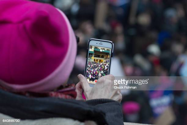 View on a cracked smart phone screen of demonstrators during the Women's March on New York as they walk along 42nd Street below the Park Avenue...