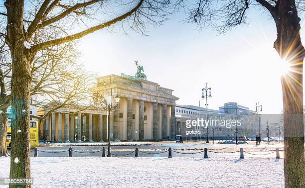 view on berlin brandenburger tor with snow in morning sun - berlin stock pictures, royalty-free photos & images