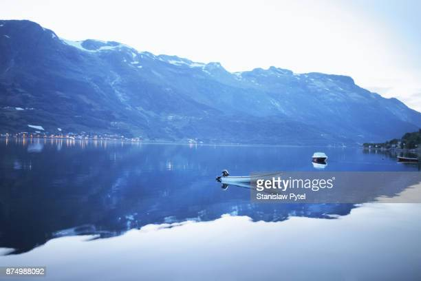 View on fjord and mountains after sunset, boats on water