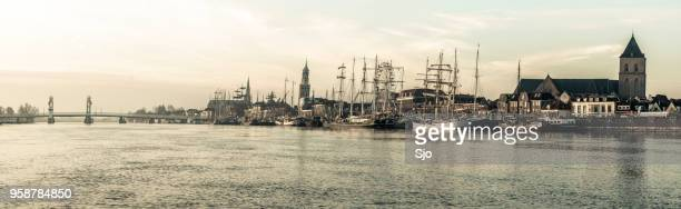 Kijk op de Kampen aan de rivier de IJssel tijdens zonsopgang met schepen afgemeerd aan de kade