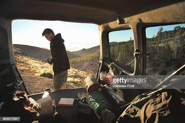view on man and mountains through car trunk - 登山用具 ストックフォトと画像