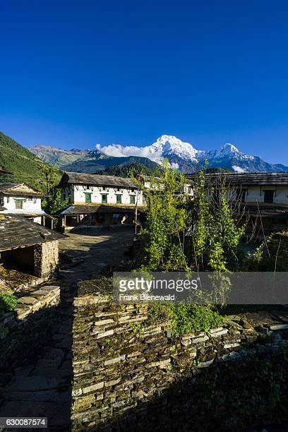View on some houses of the historical village with the mountains Annapurna South , Himchuli in the distance.