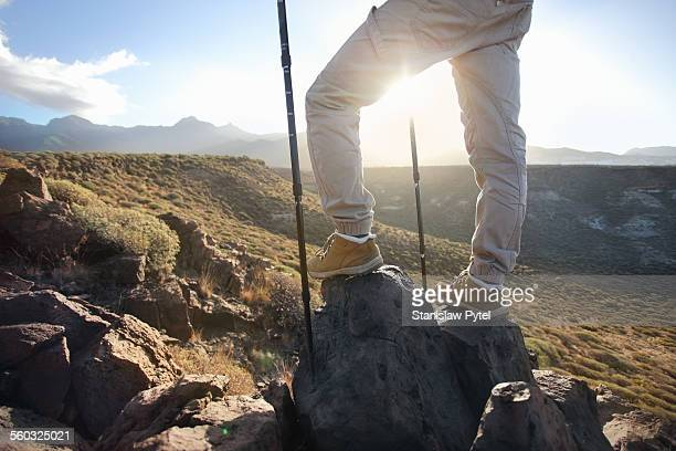 View on sunrise in mountains through legs of man