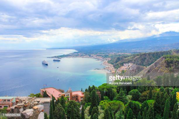 view on taormina, cruise ship in sicilian bay - taormina stock pictures, royalty-free photos & images