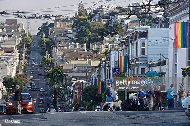CONTENT] View on the busy intersection of Market/ Castro Street in San Francisco with pedestrians and a dog crossing in the foreground and car...