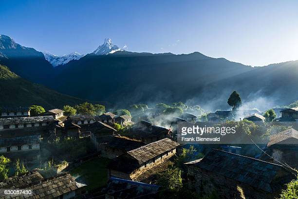 View on the historical village with the mountain Machapuchare in the distance at sunrise smok is coming out of the houses