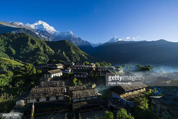 View on the historical village with the mountains Annapurna South , Himchuli and Machapuchare in the distance at sunrise, smok is coming out of the...