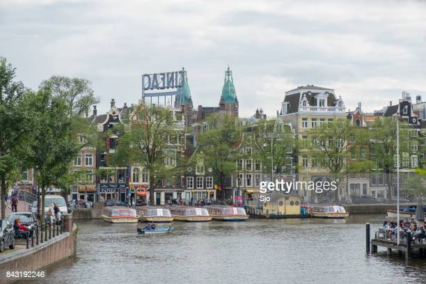 View on the river Amstel in Amsterdam with tour boats