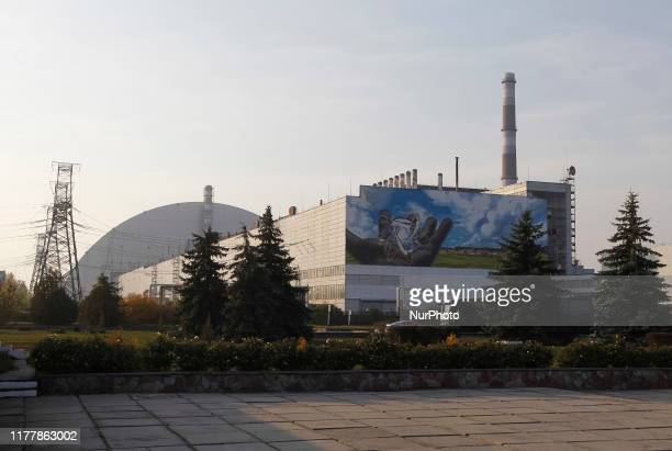 A view on the Safe Confinement over the 4th block of Chernobyl Nuclear power plant and a giant mural of author Valerii Korshunov during a press tour...