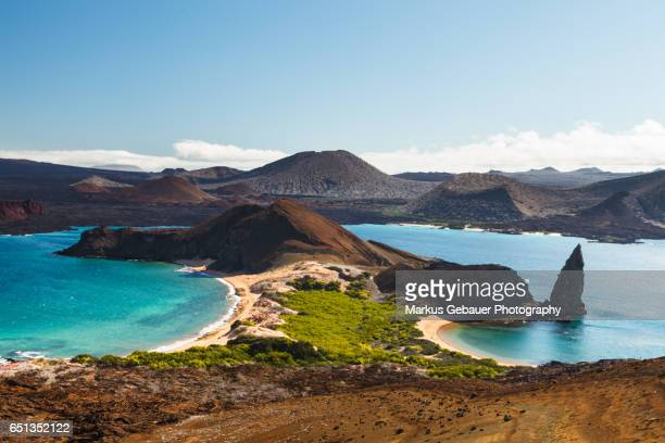 view on the volcanic landscape of bartolome island with famous pinnacle rock and golden beach, galapagos islands, ecuador - ecuador stock pictures, royalty-free photos & images