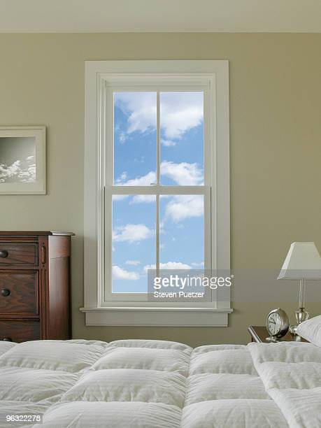 View out bedroom window with blue sky and clouds