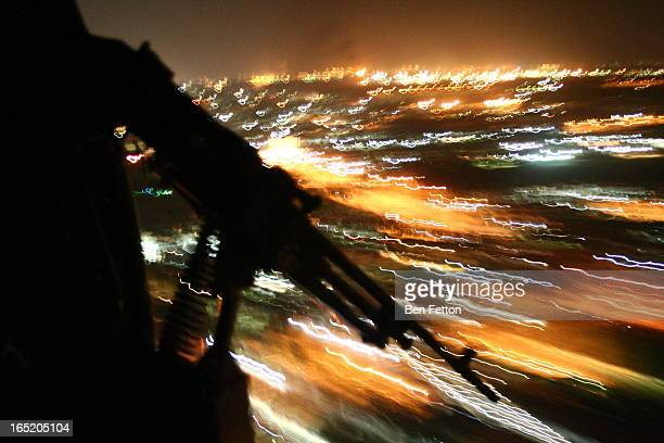 View out the door of a helicopter, flying low over Baghdad at night.