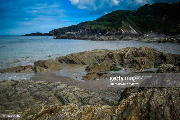 view out to sea from rocky coastline against blue sea and sky at hele bay, ilfracombe - ilfracombe stock pictures, royalty-free photos & images