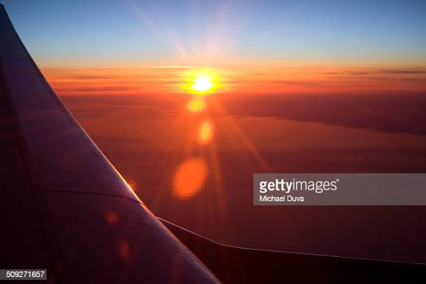 View outside an airplane window at sunset