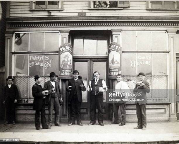 View outside Petryl's Saloon at 125 West 19th Street where a group of men stand in front with beer glasses and wine bottle Chicago IL late nineteenth...