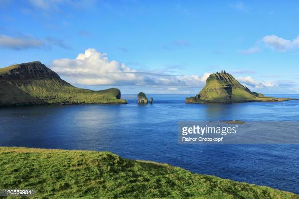 view over a meadow at the sea with several grassy and rocky islands in the background - rainer grosskopf stock-fotos und bilder