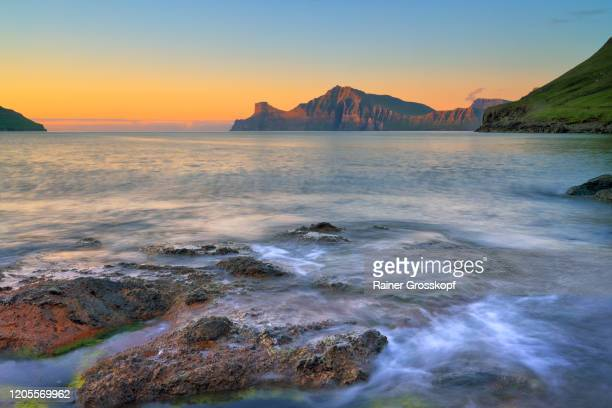 view over a rocky shore at steep and rocky mountains illuminated by the setting sun - rainer grosskopf stock-fotos und bilder