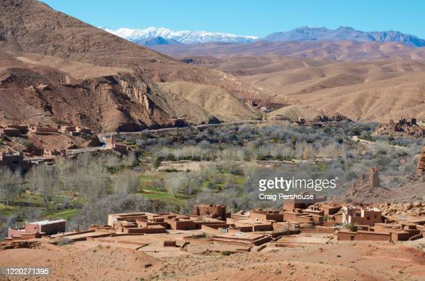 view over baked mud houses, oasis and arid mountains of the dades valley, with the snowcapped high atlas mountains in the distance. - country geographic area stock pictures, royalty-free photos & images