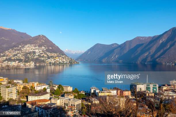 view over city and alpine lake lugano with mountain and the moon - ticino canton stock pictures, royalty-free photos & images