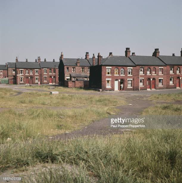 View over cleared wasteground of residential streets of Victorian era two storey terraced housing in the Harpurhey suburb of north east Manchester,...