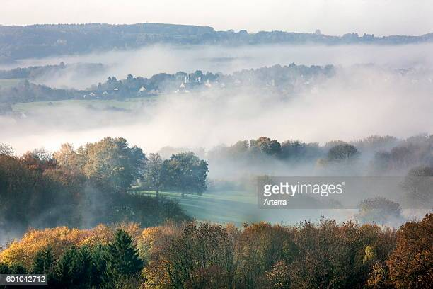 View over fileds and the village SougneRemouchamps in the mist Aywaille Liege Belgian Ardennes Belgium
