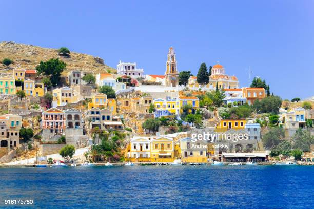 view over harbour to colourful houses and church, symi, dodecanese islands, south aegean, greece - symi foto e immagini stock