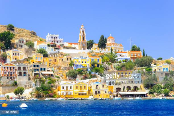 view over harbour to colourful houses and church, symi, dodecanese islands, south aegean, greece - rhodes dodecanese islands stock photos and pictures